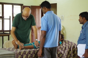 medico español revisando las piernas de un niño operado